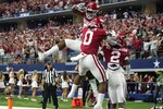 Arkansas wide receiver Trey Knox, top, AJ Green (0) and Ketron Jackson Jr. (2) celebrate a touchdown scored by Green in the first half of an NCAA college football game against Texas A&M in Arlington, Texas, Saturday, Sept. 25, 2021. (AP Photo/Tony Gutierrez)