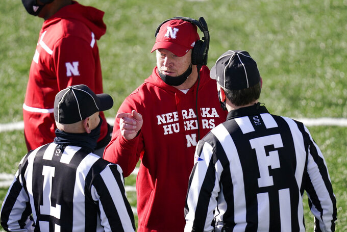 Nebraska head coach Scott Frost, center, questions a call against his team during the first half of an NCAA college football game against Iowa, Friday, Nov. 27, 2020, in Iowa City, Iowa. (AP Photo/Charlie Neibergall)