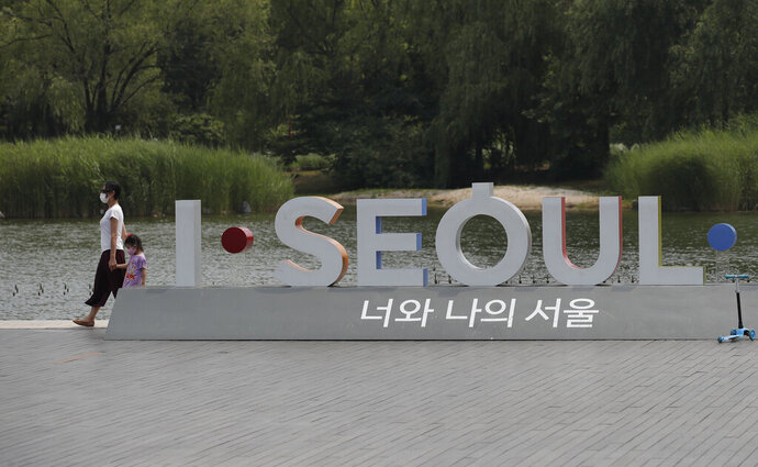 Visitors wearing face masks to prevent the spread of the new coronavirus walk at a park in Seoul, South Korea, Saturday, June 20, 2020. (AP Photo/Lee Jin-man)