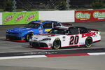 Harrison Burton (20) and Justin Allgaier (7) lead the field at the start of the NASCAR Xfinity Series auto race at Martinsville Speedway in Martinsville, Va., Friday, April 9, 2021. (AP Photo/Steve Helber)