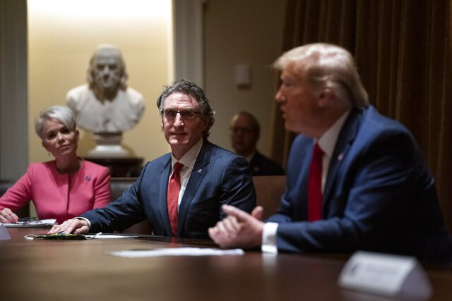 Michelle Kommer, commissioner of the North Dakota Department of Commerce, left, and North Dakota Gov. Doug Burgum, center, listen as President Donald Trump speaks during a meeting about the coronavirus response, in the Cabinet Room of the White House, Wednesday, May 13, 2020, in Washington. (AP Photo/Evan Vucci)