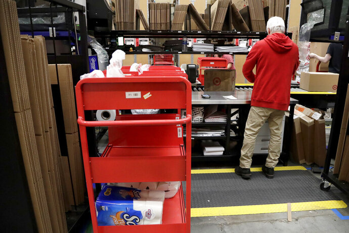 FILE- In this Nov. 16, 2018, photo an assembly line worker packages items from an online order to be shipped out of a Target store in Edison, N.J. Target is offering same-day delivery on thousands of items for $9.99 per order through a delivery startup it purchased nearly two years ago. (AP Photo/Julio Cortez, File)