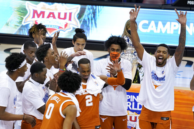 Texas guard Matt Coleman III (2) celebrates with teammates after they defeated North Carolina in an NCAA college basketball game for teh championship of the Maui Invitational, Wednesday, Dec. 2, 2020, in Asheville, N.C. (AP Photo/Kathy Kmonicek)