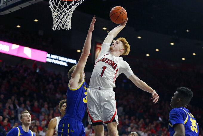Arizona guard Nico Mannion (1) dunks over South Dakota State guard Alex Arians in the second half during an NCAA college basketball game, Thursday, Nov. 21, 2019, in Tucson, Ariz. (AP Photo/Rick Scuteri)