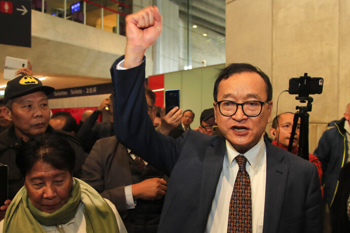 Cambodia's most prominent opposition politician Sam Rainsy clenches his fist as he is attempting to return to Cambodia Thursday, Nov. 7, 2019 at Charles de Gaulle airport, north of Paris. Sam Rainsy is attempting to return to Cambodia from his self-imposed exile to force out the long-serving leadership but may not be let on Thursday's Paris-Bangkok flight. (AP Photo/Michel Euler)