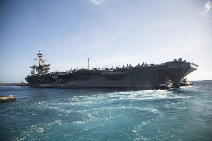 In this photo provided by the U.S. Marine Corps, the aircraft carrier USS Theodore Roosevelt (CVN 71) departs Apra Harbor at Naval Base Guam on Thursday, May 21, 2020, following an extended visit to Guam in the midst of the COVID-19 pandemic. The ship left Guam on Thursday and went out to sea for training after nearly two months sidelined at the pier with a coronavirus outbreak. (Staff Sgt. Jordan E. Gilbert/U.S. Marine Corps via AP)