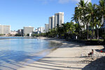 FILE — In this Oct. 2, 2020, file photo, a man sits on a nearly empty Waikiki Beach in Honolulu before the state reopened its economy. After loosening rules, health care workers in Hawaii now say a lack of government action is worsening an already crippling surge of coronavirus cases in the islands, and without effective policy changes the state's limited hospitals could face a grim crisis. (AP Photo/Caleb Jones, File)