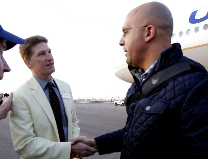 FILE - In this Dec. 23, 2017, file photo, Penn State head coach James Franklin, right, is greeted by Fiesta Bowl executive director Mike Nealy in preparation for an upcoming NCAA college football bowl game against Washington in Phoenix. Nealy and the Fiesta Bowl organizing committee faced unique challenges this year running two games. The Fiesta Bowl, one of the New Year's Six bowl games, went off as planned but the Guaranteed Rate Bowl, which was scheduled for Dec. 26, 2020, was canceled after there weren't enough teams to fill all of the bowl spots. (AP Photo/Rick Scuteri, File)