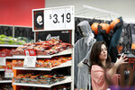FILE- In this Oct. 3, 2018, file photo Sophia Narvaez, looks at Halloween decorations at a Target department store in Pembroke Pines, Fla. On Thursday, Oct. 11, the Labor Department reports on U.S. consumer prices for September. (AP Photo/Brynn Anderson, File)
