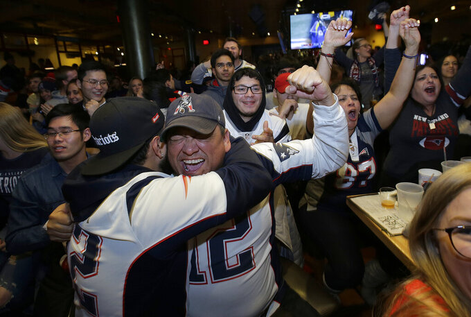 New England Patriots fan Victor Polanco, center, cheers with others while watching the second half of the NFL Super Bowl 53 football game in Atlanta between the Patriots and the Los Angeles Rams at a bar in Boston, Sunday, Feb. 3, 2019. (AP Photo/Steven Senne)