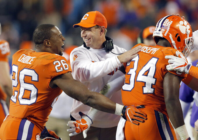 FILE - In this Dec. 2, 2017, file photo, Clemson head coach Dabo Swinney, center, congratulates his players during the second half of the Atlantic Coast Conference championship NCAA college football game against Miami, in Charlotte, N.C. The Tigers are pursuing their fourth straight Atlantic Coast Conference championship and have lost two league games in three seasons. (AP Photo/Bob Leverone, File)