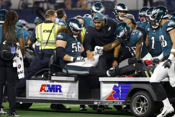 Members of the Philadelphia Eagles team and staff support guard Isaac Seumalo (56) as he is carted off the field after suffering an unknown injury in the second half of an NFL football game against the Dallas Cowboys in Arlington, Texas, Monday, Sept. 27, 2021. (AP Photo/Ron Jenkins)