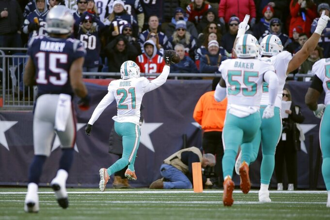 Miami Dolphins cornerback Eric Rowe, center, runs back an interception for a touchdown in the first half of an NFL football game against the New England Patriots, Sunday, Dec. 29, 2019, in Foxborough, Mass. (AP Photo/Elise Amendola)