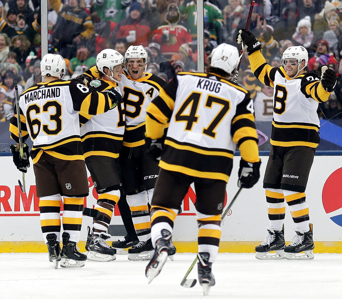 Boston Bruins center Patrice Bergeron (37), center, celebrates with teammates after scoring his goal in the second period of the NHL Winter Classic hockey game against the Chicago Blackhawks at Notre Dame Stadium, Tuesday, Jan. 1, 2019, in South Bend, Ind. (AP Photo/Nam Y. Huh)