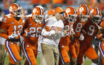 FILE - In this Dec. 2, 2017, file photo, Clemson head coach Dabo Swinney, center, links arms with players as they march on the field before the Atlantic Coast Conference championship NCAA college football game against Miami in Charlotte, N.C. The second-ranked Tigers will face Pittsburgh for the ACC title on Saturday night. Swinney says the ACC title game experience will help the Tigers.  (AP Photo/Bob Leverone, File)