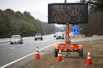 A sign instructs motorists with New York license plates to pull over at a checkpoint on I-95 over the border from Connecticut where New Yorkers must pull over and provide contact information and are told to self-quarantine for two weeks, Saturday, March 28, 2020, in Hope Valley, R.I. Rhode Island Gov. Gina Raimondo on Saturday ordered anyone visiting the state to self-quarantine for 14 days and restricted residents to stay at home and nonessential retail businesses to close Monday until April 13 to help stop the spread of the coronavirus. (AP Photo/David Goldman)