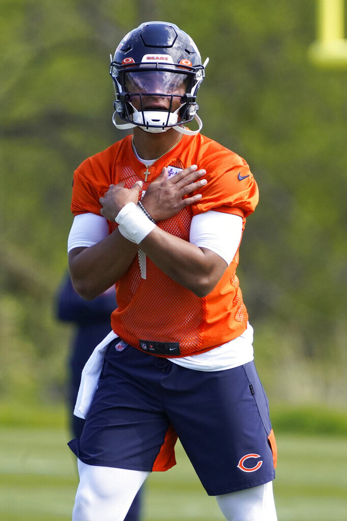 Chicago Bears quarterback Justin Fields (1) signals during drills in the NFL football team's rookie minicamp Friday, May, 14, 2021, in Lake Forest Ill. (AP Photo/David Banks, Pool)