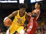 Minnesota's Daniel Oturu (25) drives against Wisconsin's D'Mitrik Trice during the first half of an NCAA college basketball game Wednesday, Feb. 5, 2020, in Minneapolis. (AP Photo/Hannah Foslien)