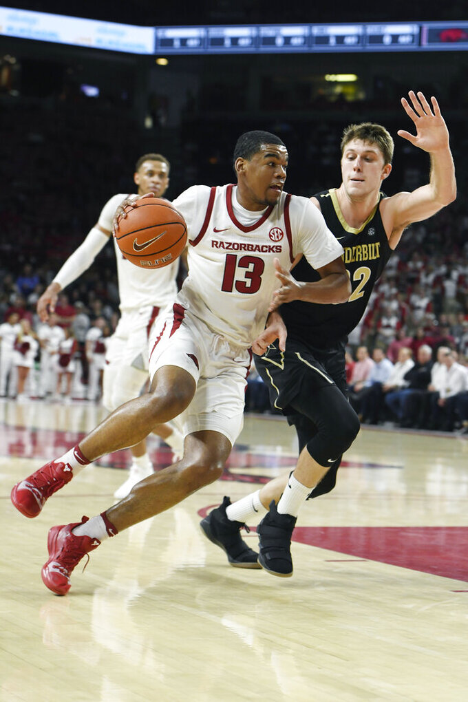 Arkansas guard Mason Jones (13) tries to get past Vanderbilt defender Matt Ryan (32) during the first half of an NCAA college basketball game, Tuesday, Feb. 5, 2019 in Fayetteville, Ark. (AP Photo/Michael Woods)