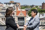 """In this May 21, 2021, photo overlooking the Dupont Circle neighborhood, Washington based civil rights attorneys Lisa Banks, left, and Debra Katz chat after a portrait session at their law firm in Washington. For many people, the pandemic year has brought a pause of some kind, or at least a slowdown, to their professional endeavors. For Katz and Banks, the opposite has been true. """"This is probably the biggest year we've ever had,"""" says Banks.  Their work has been increasing for nearly four years. When the Harvey Weinstein revelations erupted in October 2017,  launching the reckoning that became known as the #MeToo movement, it caused """"a sea change,"""" Katz says. (AP Photo/Jacquelyn Martin)"""