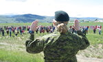 Royal Canadian Air Force Public Affairs Officer Lt. Alexandra Hejduk reacts to a First Nations drummers salute during a drum ceremony to remember fallen Snowbirds Capt. Jenn Casey in Kamloops, B.C., Monday, May 18, 2020. Capt.Casey died Sunday after the Snowbirds jet she was in crashed shortly after takeoff. The pilot of the aircraft is in hospital with serious injuries. (Jonathan Hayward/The Canadian Press via AP)