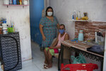 Rachel de Lima Ribeiro, who recovered from COVID-19, poses for a photo with her handicapped husband Felipe da Silva inside their small home in the Mare Complex favela in Rio de Janeiro, Brazil, Thursday, April 8, 2021. Ribeiro, who used to sell sweetmeats, lost her livelihood during the pandemic and now the couple eats thanks to donations. (AP Photo/Silvia Izquierdo)