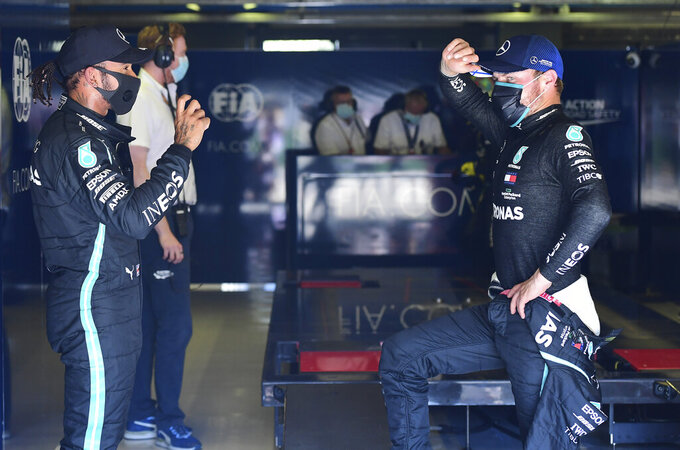 Mercedes driver Lewis Hamilton, left, of Britain talks with his teammate Valtteri Bottas of Finland after clocking the fastest time during the qualifying session for Sunday's Italian Formula One Grand Prix, at the Monza racetrack in Monza, Italy, Saturday, Sept. 5, 2020. (Jennifer Lorenzini/Pool via AP)