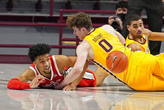 Ohio State's Justice Sueing, left, gets off a pass despite a collision with Minnesota's Liam Robbins in the first half of an NCAA college basketball game Sunday, Jan. 3, 2021, in Minneapolis. (AP Photo/Jim Mone)
