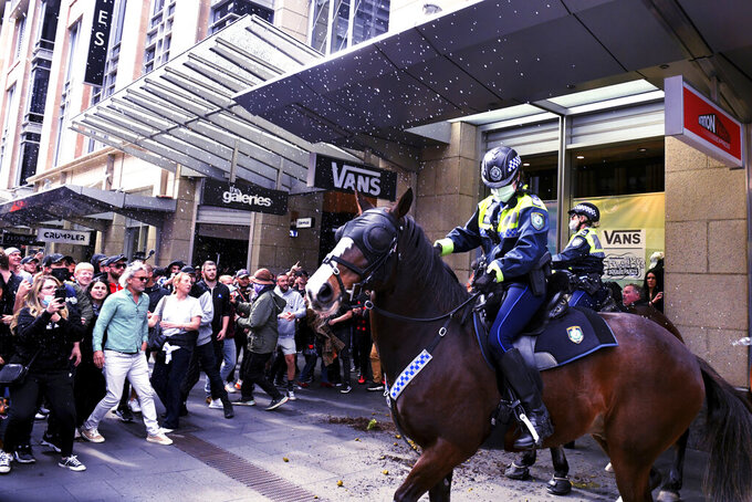 Protesters and mounted police clash at Sydney Town Hall during a 'World Wide Rally For Freedom' anti-lockdown rally in Sydney, Saturday, July 24, 2021. (Mick Tsikas/AAP Image via AP)