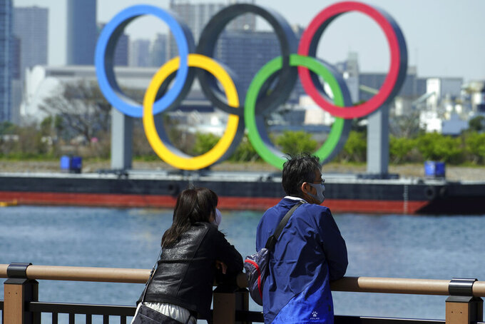 "A man and a woman stand with a backdrop of the Olympic rings floating in the water in the Odaiba section Thursday, March 18, 2021, in Tokyo. Tokyo Olympics creative director Hiroshi Sasaki is resigning after making demeaning comments about Naomi Watanabe, a well-known female celebrity. Sasaki who was in charge of the opening and closing ceremonies for the Olympics, told planning staff members last year that Watanabe could perform in the ceremony as an ""Olympig."" (AP Photo/Eugene Hoshiko)"