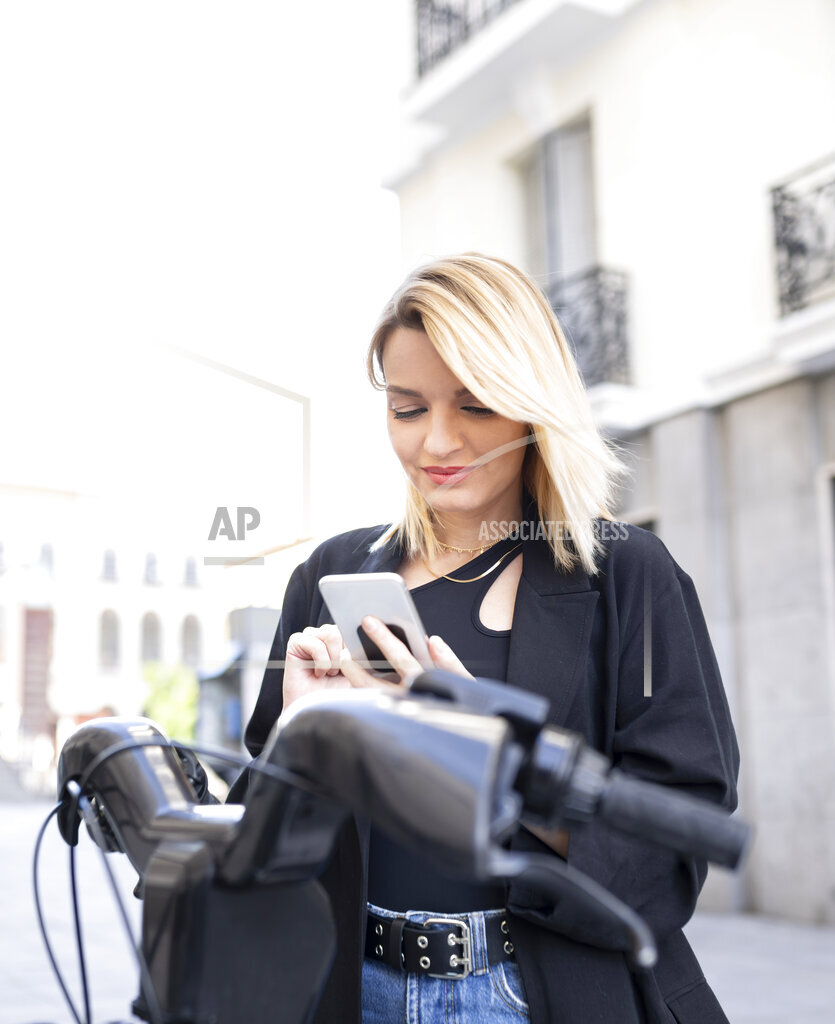 Blond woman using mobile phone in front of electric vehicle
