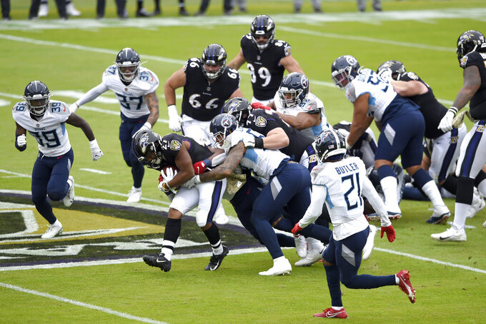 Baltimore Ravens running back J.K. Dobbins (27) runs with the ball as a host of Tennessee Titans players try to stop him during the first half of an NFL football game, Sunday, Nov. 22, 2020, in Baltimore. (AP Photo/Gail Burton)