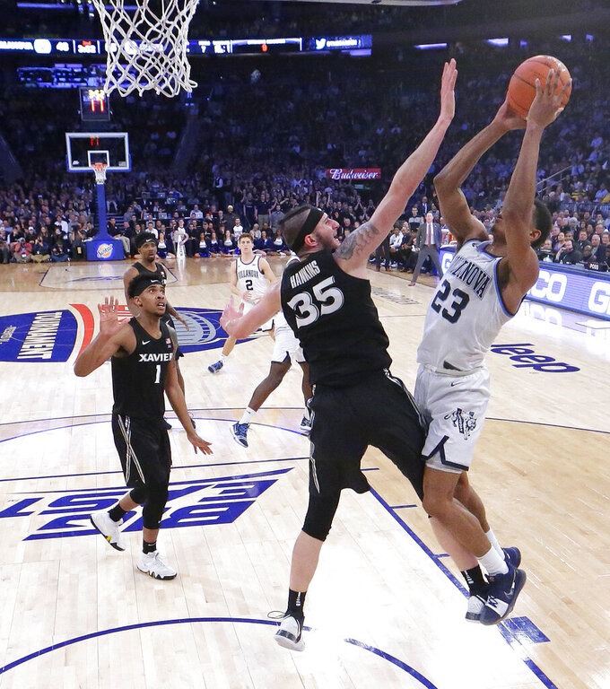 Villanova forward Jermaine Samuels (23) goes up for a shot against Xavier forward Zach Hankins (35) during the second half of an NCAA college basketball semifinal game in the Big East men's tournament, Friday, March 15, 2019, in New York. (AP Photo/Julio Cortez)