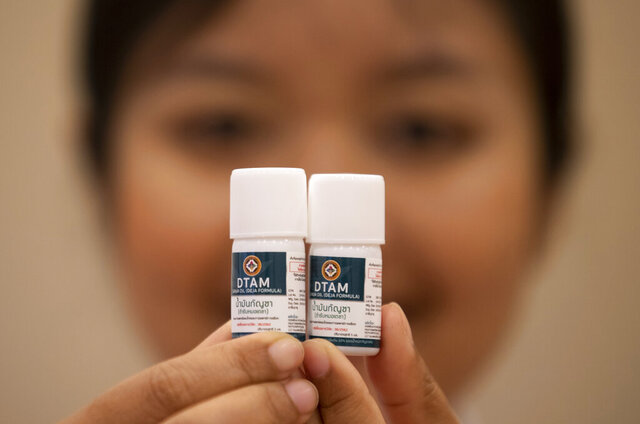 A doctor show containers of cannabis oil at the first full-time clinic prescribing cannabis oil for medical treatment in the Public Health Ministry in Nonthaburi province, Thailand, Monday, Jan. 6, 2020. The opening of the clinic is another step forward in the government's policy of promoting the licensed medical use of marijuana products to relieve the symptoms of a range of conditions. (AP Photo/Sakchai Lalit)