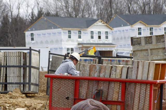 Construction continues at a housing plan in Zelienople, Pa., Wednesday, March 18, 2020.  Economic and housing market trends at the start of the year both favored U.S. homebuilders' prospects for 2020. That was then. But with the coronavirus outbreak now expected to tip the U.S. into recession, the National Association of Home Builders projects that new home construction and sales will take a hit as efforts to contain its spread disrupt large swaths of the economy.  (AP Photo/Keith Srakocic)