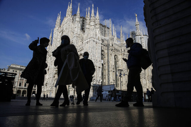 People wear masks to curb the spread of COVID-19 as they walk next to the Duomo gothic cathedral, in Milan, Italy, Friday, Oct. 16, 2020. Italian health officials have declared the country in an