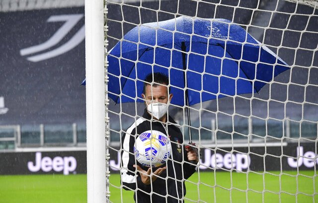 Referee Daniele Doveri inspects the pitch of the Allianz Stadium in Turin, Italy, Sunday, Oct. 4, 2020 ahead of the scheduled Serie A soccer match between Juventus and Napoli. Napoli is likely to be handed a 3-0 loss by the Italian league's judge for failing to show for its Serie A match at Juventus on Sunday night. Napoli did not travel to Turin for the match after local health authorities ordered the squad into quarantine after two players tested positive for the coronavirus. (Tano Pecoraro/LaPresse via AP)