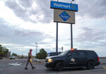 FILE - In this Aug. 4, 2019 file photo, a Texas State Trooper walks back to his car while providing security outside the Walmart store in the aftermath of a mass shooting in El Paso, Texas. A gunman who said he was targeting Mexicans and killed 22 people at a Walmart store in El Paso, Texas, over the summer has been indicted on federal hate crimes charges, a person familiar with the matter told The Associated Press. (AP Photo/Andres Leighton)