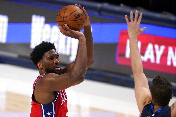 Philadelphia 76ers center Joel Embiid (21) takes a shot over Dallas Mavericks forward Maxi Kleber, right, in the second half of an NBA basketball game in Dallas, Monday, April 12, 2021. (AP Photo/Tony Gutierrez)
