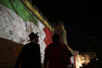 A couple walks past representations of the Emirati and Bahraini flags projected onto the walls of Jerusalem's Old City, marking the day of a signing ceremony in Washington signifying the two Gulf nations' normalization of relations with Israel, Tuesday, Sept. 15, 2020. (AP Photo/Maya Alleruzzo)
