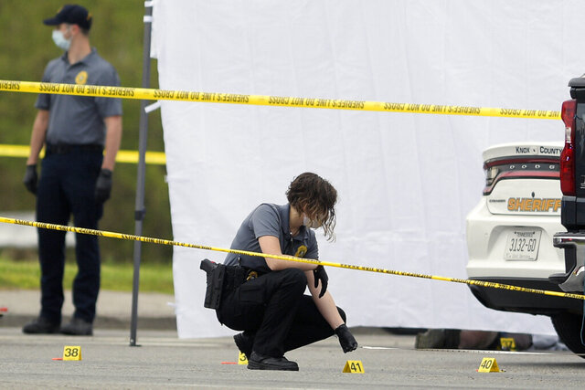 An investigator takes measurements at the scene of a multi-victim stabbing at a Pilot truck stop on Strawberry Plains Pike in Knoxville, Tenn. on Tuesday, April 7, 2020. A man fatally stabbed three employees and wounded a customer at a Tennessee rest stop and travel center Tuesday morning before a deputy shot and killed him, authorities said.(Calvin Mattheis/Knoxville News Sentinel via AP)