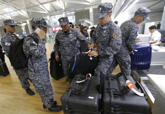 South Korean navy rescue team members prepare to board a plane to leave for Budapest at Incheon International Airport in Incheon, South Korea, Thursday, May 30, 2019. A massive search is underway on the Danube River in downtown Budapest for over a dozen people missing after a sightseeing boat with 33 South Korean tourists sank after colliding with another vessel during an evening downpour. (AP Photo/Ahn Young-joon)