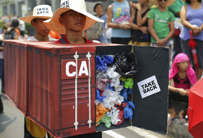 FILE - In this May 7, 2015, file photo, Filipino environmental activists wear a mock container vans filled with garbage to symbolize the 50 containers of waste that were shipped from Canada to the Philippines two years ago, as they hold a protest outside the Canadian embassy at the financial district of Makati, south of Manila, Philippines. The Philippine foreign secretary said Thursday, May 16, 2019, the ambassador and consuls in Canada are being recalled over Ottawa's failure to take back truckloads of garbage that Filipino officials say were illegally shipped to the Philippines years ago. (AP Photo/Aaron Favila, File)