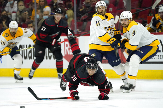 Carolina Hurricanes right wing Sebastian Aho (20) is tripped while skating near Nashville Predators left wing Filip Forsberg (9) and center Luke Kunin (11) during the second period in Game 5 of an NHL hockey Stanley Cup first-round playoff series in Raleigh, N.C., Tuesday, May 25, 2021. (AP Photo/Gerry Broome)
