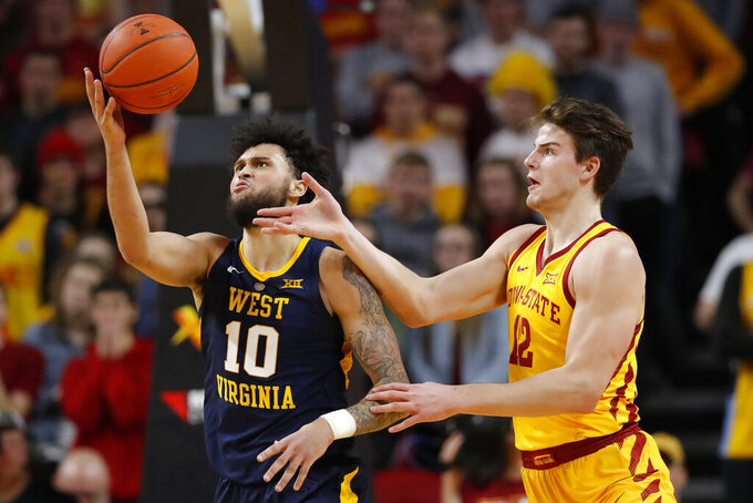 West Virginia guard Jermaine Haley (10) grabs a rebound in front of Iowa State forward Michael Jacobson during the second half of an NCAA college basketball game Wednesday, Jan. 30, 2019, in Ames, Iowa. (AP Photo/Charlie Neibergall)