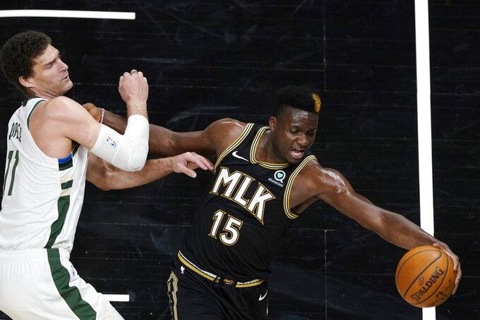 Atlanta Hawks center Clint Capela (15) reaches for the ball next to Milwaukee Bucks center Brook Lopez (11) during the second half of an NBA basketball game Thursday, April 15, 2021, in Atlanta. (AP Photo/John Bazemore)