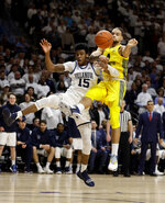 Villanova's Saddiq Bey (15) and Marquette's Theo John (4) leap for a rebound during the first half of an NCAA college basketball game, Wednesday, Feb. 27, 2019, in Villanova, Pa. (AP Photo/Matt Slocum)
