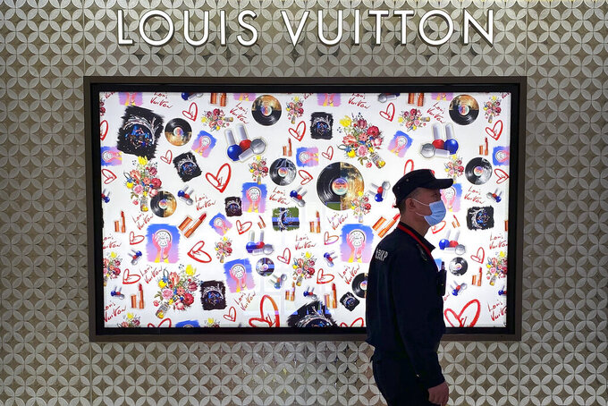 A security guard walks past a Louis Vuitton store at a shopping mall in Beijing, Tuesday, July 20, 2021. A popular Chinese-Canadian singer, Kris Wu, has lost endorsement and other deals with at least 10 brands including Porsche and Bulgari after a teen-ager accused him of having sex with her while she was drunk. (AP Photo/Mark Schiefelbein)
