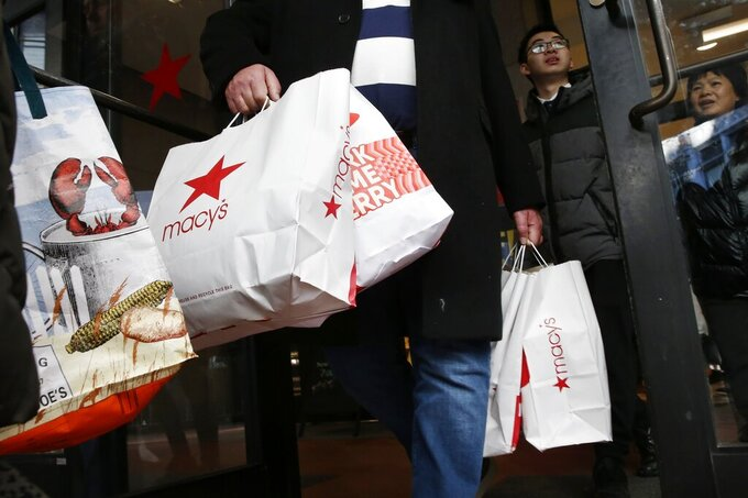 FILE - In this Friday, Nov. 29, 2019 file photo, shoppers leave Macy's in Boston. This year's Black Friday shopping event will be much different from ever before. Retailers will be enforcing social distancing, many stores will be closed on Thanksgiving Day and shoppers will be scooping up deals via their computer screens.  (AP Photo/Michael Dwyer, File)
