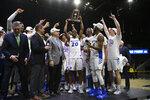 Hofstra guard Jalen Ray (20) and others raise the trophy after defeating Northeastern in an NCAA college basketball game for the championship of the Colonial Athletic Association men's tournament Tuesday, March 10, 2020, in Washington. Hofstra won 70-61. (AP Photo/Nick Wass)